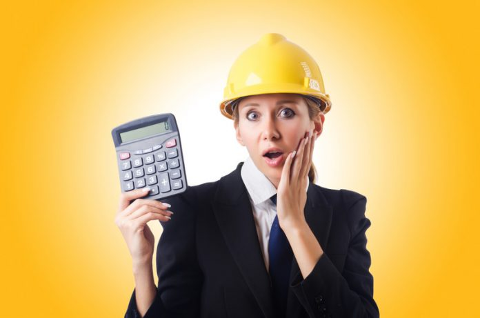 woman with hardhat and calculator